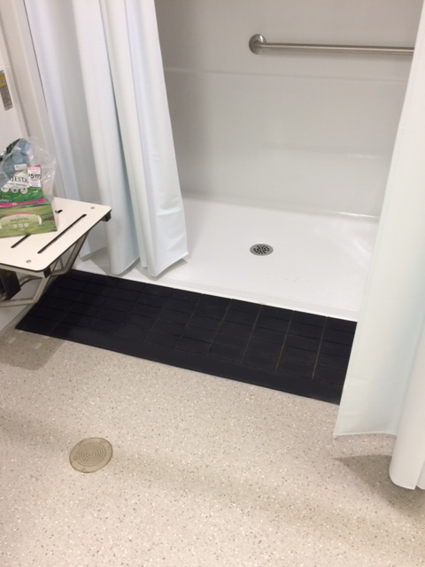ADA compliant shower ramp providing safe roll in shower access for elderly and disabled users, and to help caregivers